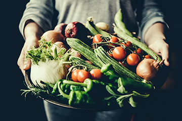 A photo of a basket of vegetables held in a persons arms